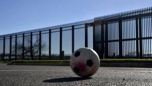 Muro Uma bola de futebol é deixada em uma rua em frente a cerca de metal, que marca a fronteira entre os Estados Unidos e o México, em Eagle Pass, no Texas. Foto: Yuri Cortez / AFP