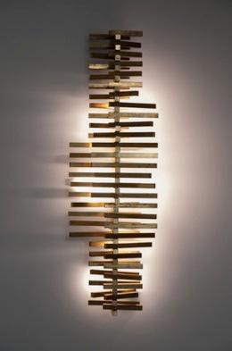 Wall lamp with tubular brass oxidized inserts and LED light.