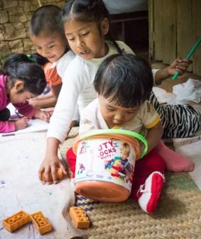 bebé jugando con cubos sobre petate