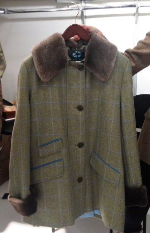 This Good Shot Design piece features high-style finishes including a beaver pelt collar, bright trims and statement buttons