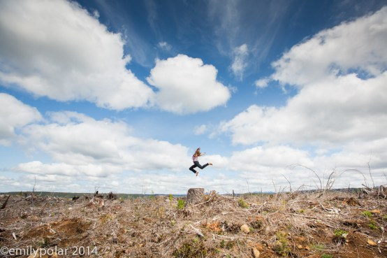 Woman doing yoga on tree stump in clear cut forest of rural Oregon.