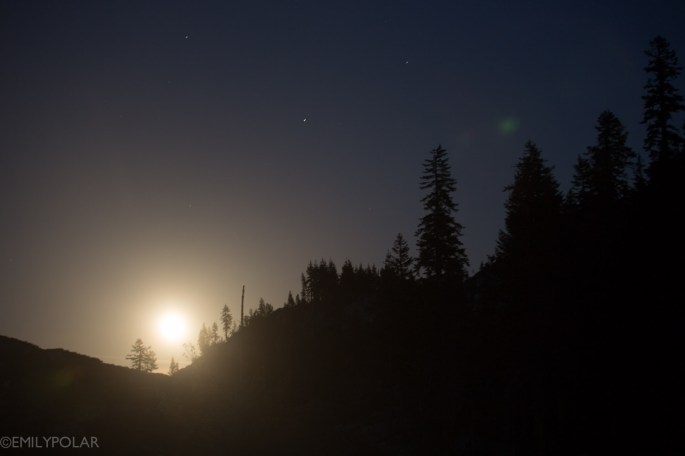 Full moon rising over mountain above trees at Heart Lake in Shasta.