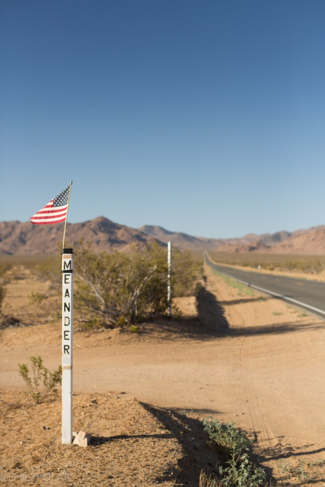 Sign post with an American flag at a driveway along Hwy 62