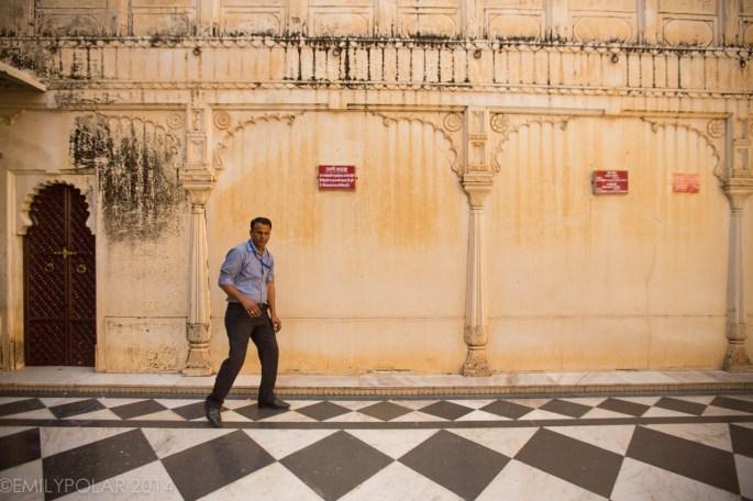 Indian man walking akwardly along one of the City Palace walls in Udaipur.