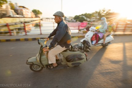 Indian man on a scooter buzzing over the bridge at sunset in Udaipur.