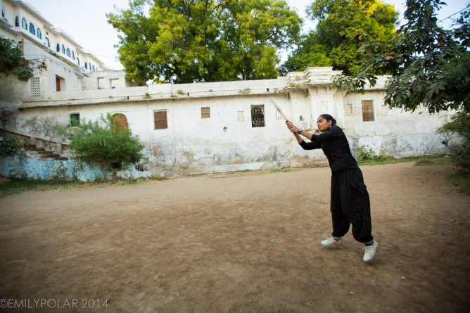 Young Indian woman playing cricket in a dirt court below home in Udaipur.