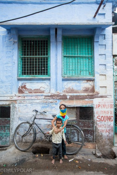 Indian kids pose next to bicycle outside of their home in Jodhpur, Rajasthan.