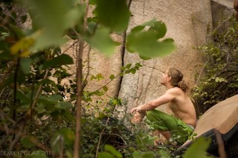 Man sitting on crash pad looking up at crack in boulder in Hampi.