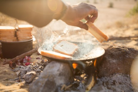 Sliced white bread toasting in round pan over fire in the morning sun of the Thar Desert.
