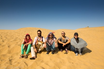 Group of friends sitting in the sand and sun of the Thar desert of Rajasthan.