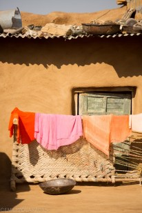 Colorful laundry hanging out in the sun of a mud home in rural village in Thar desert near Jaisalmer.