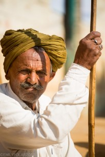 Rajasthani man with cane and sun shining on face while sitting in front of hus mud home in a small village of Thar desert, India.