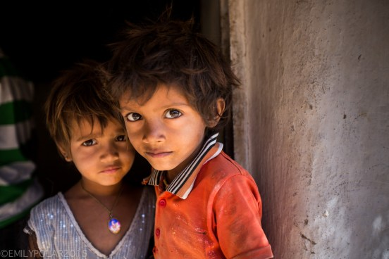 Portrait of brother and sister in doorway at their home deep in the Thar Desert of Rajasthan.
