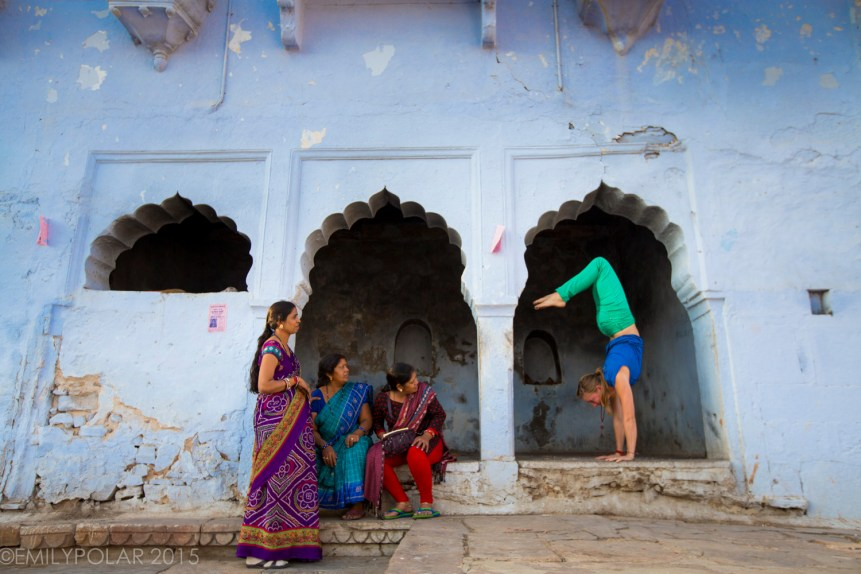 Blonde woman in green pants doing handstand in arch near the ghats in Pushkar while Indian woman watch.