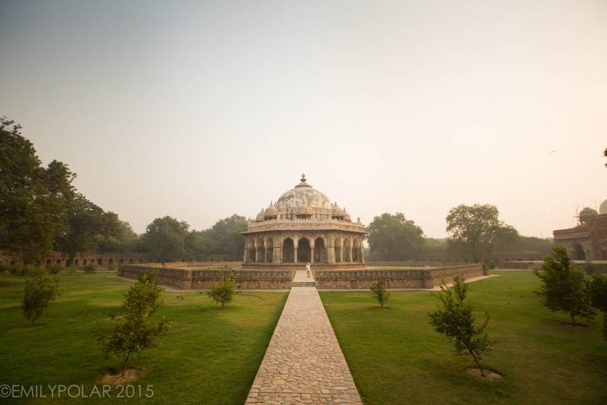 Western tourist walking around the grounds at Humayuns Tomb in Delhi.