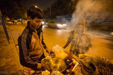 Young Indian boy working as a street vendor near Kalka Mandir in Delhi, India.
