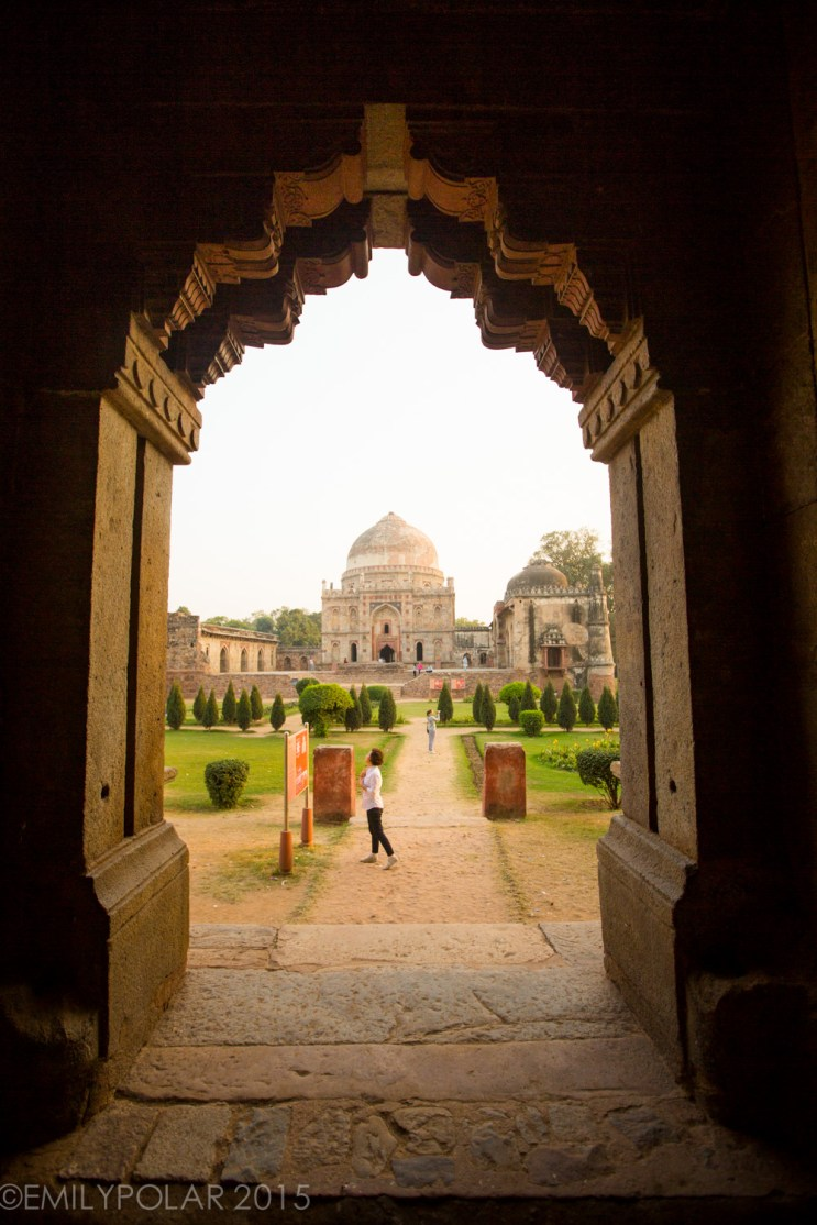 Asian woman looking at a sign outside of Bara Gumbad tomb and mosque in Lodi Gardens, Delhi.