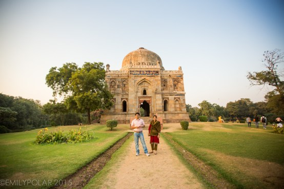 Indian tourists visiting Bara Gumbad tomb and mosque smiling for a photo at Lodi Gardens, Delhi.