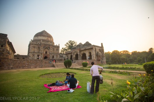 Indian man serving chai to Indian couple resting on the green grass in front of Bara Gumbad tomb and mosque at Lodi Gardens, Delhi.