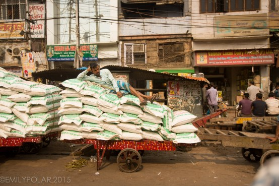 Indian man laying down on bags of spices stacked high on a wooden cart at the spice market in Old Delhi, India.