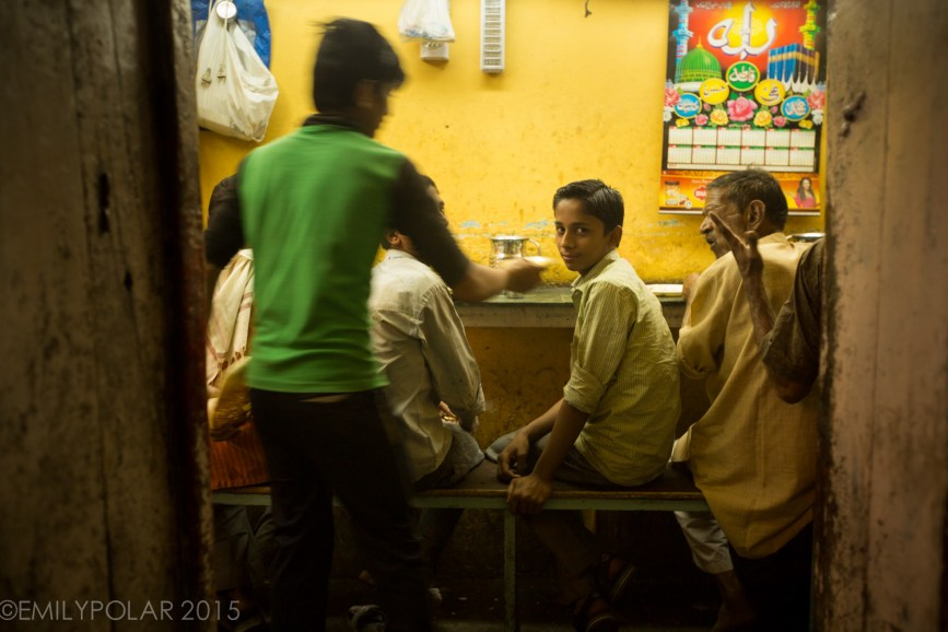 Young Indian boys sitting on a bench eating at a local resturant in Old Delhi, India.