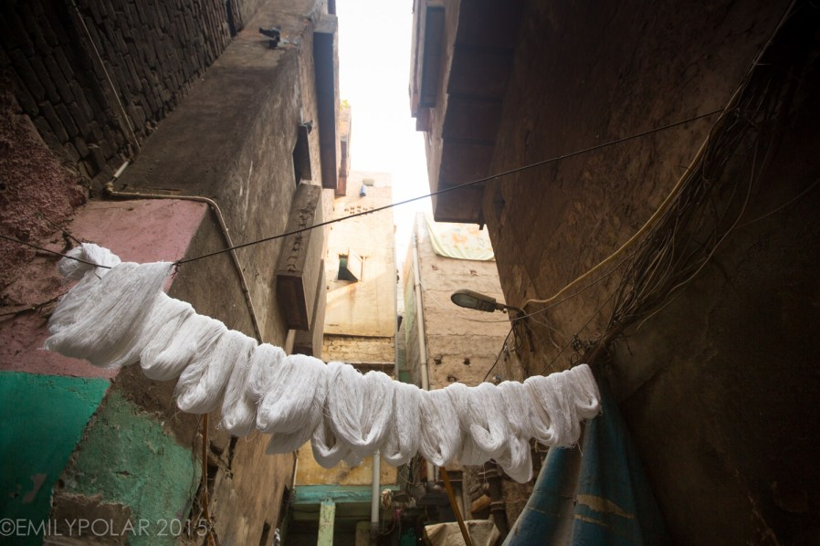 Neighborhood doing laundry in alley of Old Delhi, India.