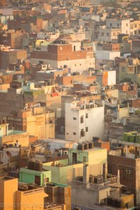 Aerial view from the Jama Masjid Tower of Old Delhi cement homes stacked next to each other in crowded urban spaces of India.