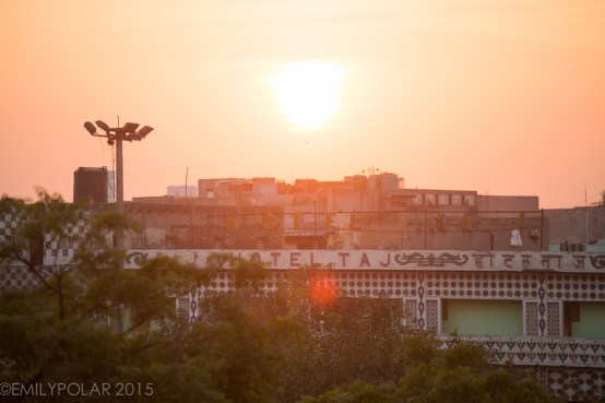 Hotel Taj in Old Delhi lit by the setting sun through the haze of urban layers in India.