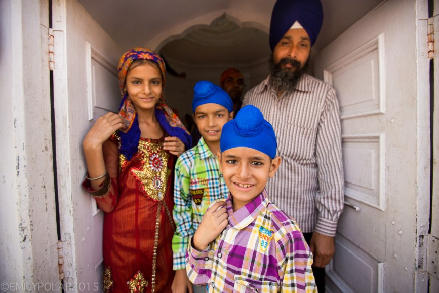 Portrait of a Punjabi Family smiling at the Golden Temple in Amritsar.