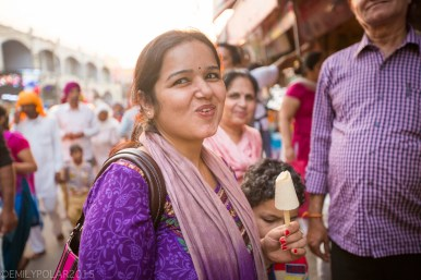 Indian woman enjoying a frozen treat in the streets of Amritsar.