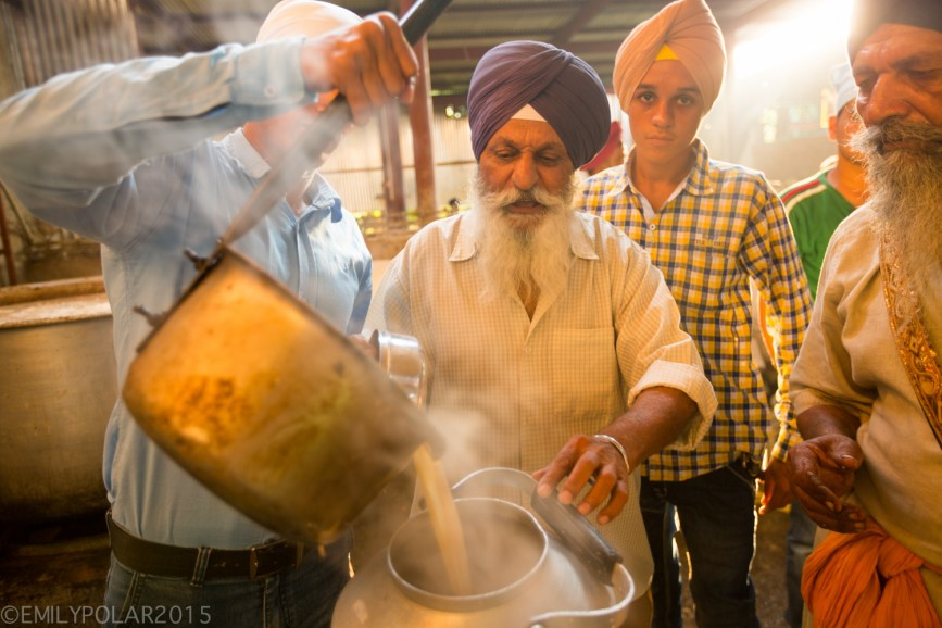 Indian men working the chai station where huge pots cook milk and tea then poured into large metal tea pots at the Golden Temple.