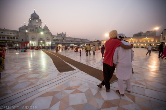Two Indian men stand with their arms around each others shoulders at the Golden Temple.
