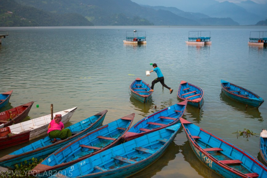 Nepali man jumping from one boat to another to clean out the water from a days work on Pokhara Lake, Nepal.