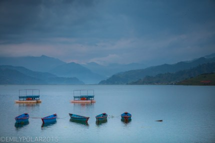 Wooden blue boats floating on Pokhara lake on a cloudy day in Nepal.