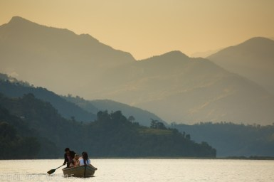 Tourists in wooden boat touring around Pokhara Lake in the Himalayas of Nepal.
