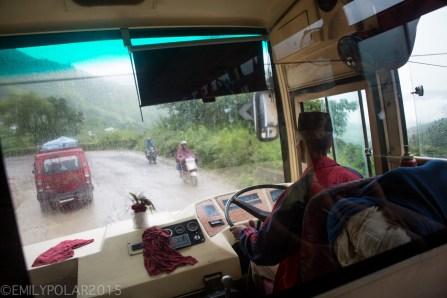 Nepali bus driver turning the big wheel steering us through the rain and mud.