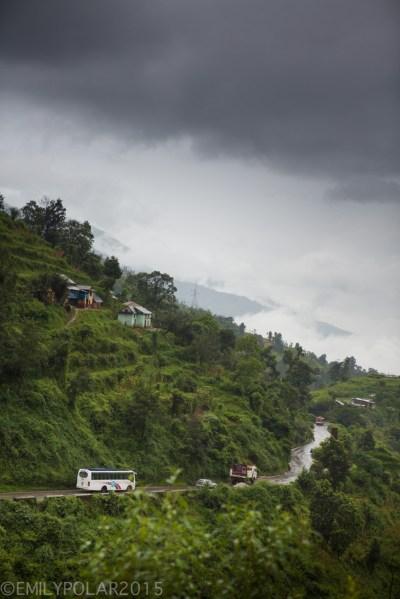 Curvy road winding from Kathmandu to Pokhara through the green lush and rainy hillside of Nepal.