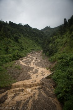 Muddy rain water flowing down rocky run off stream on the way to Pokhara, Nepal.