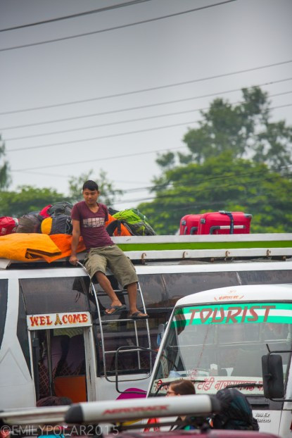 Nepali man loading bags on top of tourist bus in Pokhara, Nepal.