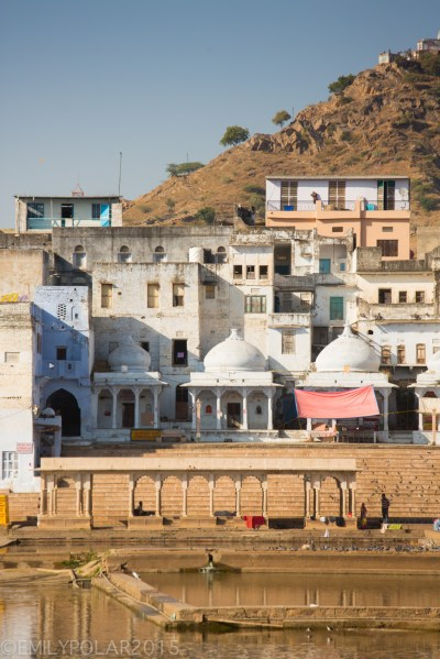 Pushkar lake surrounded by holy ghats, temples, guest houses and forts with a view of the Saraswati Temple in Pushkar, Rajasthan.