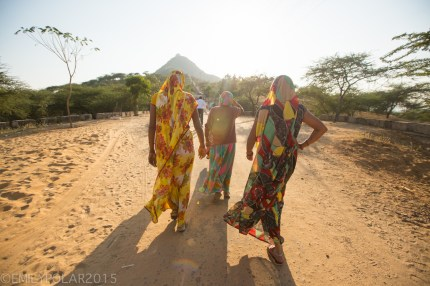 Indian women wearing colorful sari's walk along path to hill temple in Pushkar, India.