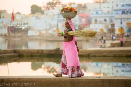 Indian woman wearing colorful sari carrying metal bowl of laundry on her head while walkign along the Ghats at Pushkar Lake.