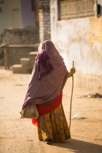 Indian woman covered in fabric walking down a dusty street in Pushkar through golden morning light with a walking stick.