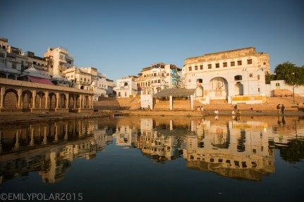 Low light sunset reflects the temples of the east end of Pushkar Lake during the golden hour in Rajasthan, India.