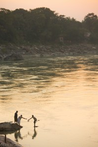 Indian men gathering water from the Ganges river and bottling it at sunset in Rishikesh.