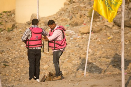 Two Indian men helping eachother put on hot pink life jackets for a boat ride on the Ganges, India.