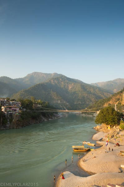 People haning out on the beach below Laxman Jhula bridge in Rishikesh, India.