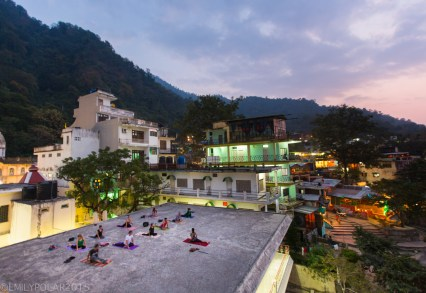 Woman yoga teacher leading a class on a rooftop in Laxman Jhula, Rishikesh.