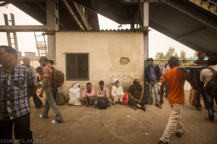 Men sitting on the ground against a mud building at a train station in Northern India.