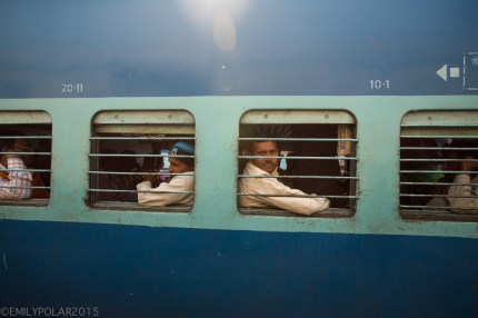 Indian men on blue train in northern India looking out the window.